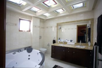 Το μπάνιο του κύριου υπνοδωματίου με γυάλινο βιτρό στην οροφή και τζακούζι.